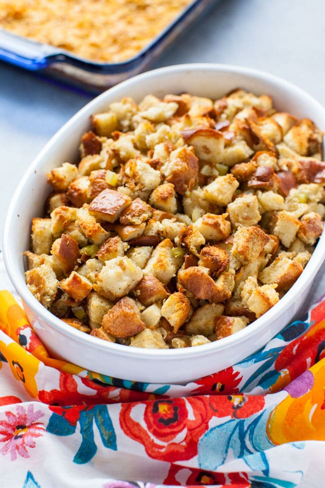 best stuffing recipe in a round baking dish with a colorful floral kitchen towel in the foreground
