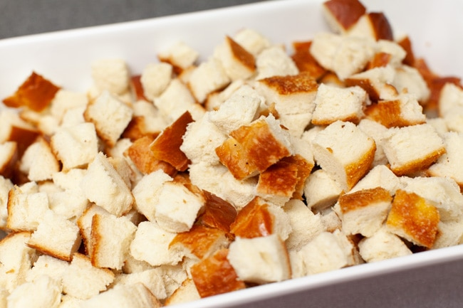 cut up bread in a white baking dish for best stuffing recipe