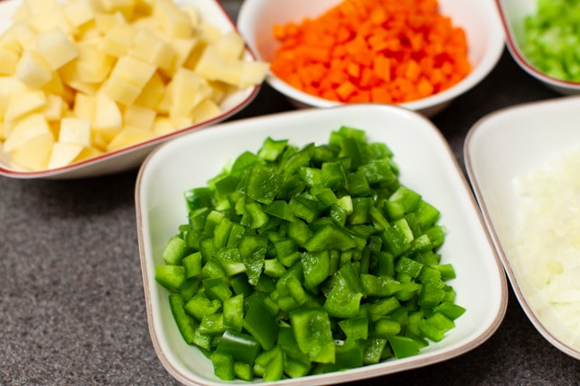 chopped green peppers and other vegetables in the background