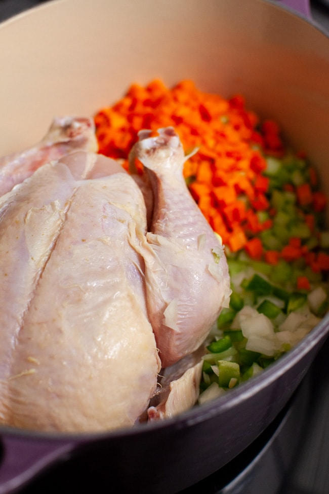 a whole chicken in a pot with chopped carrots, celery and onions