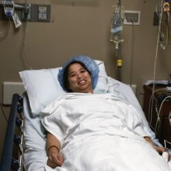 a woman laying in a hospital bed with a hair net on with white blankets