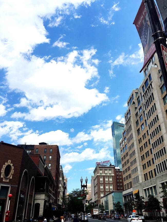photo of a Boston street with towering buildings and a blue sky