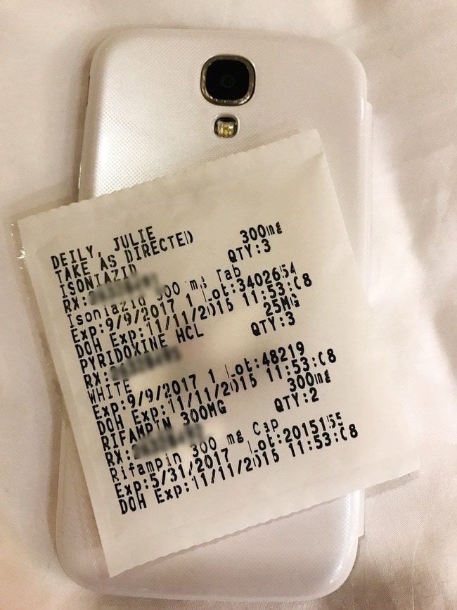 Medications in a plastic bag with writing and a white smart phone