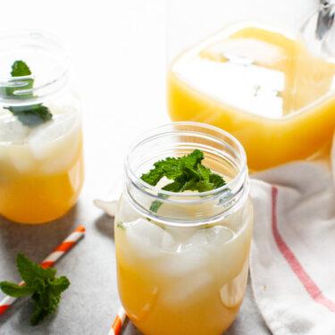 orange mint tea in a mason jar with straws