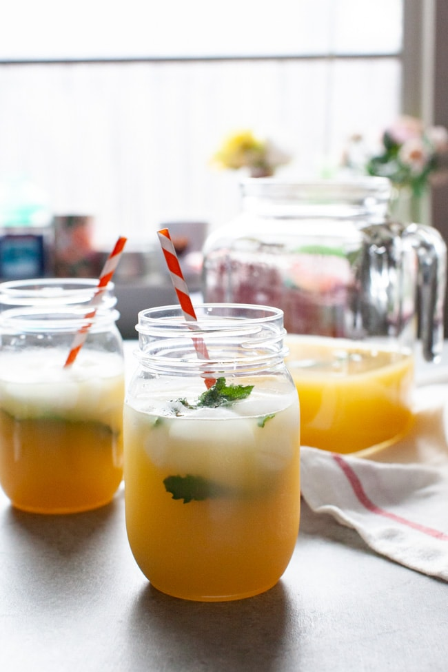 orange mint tea in mason jars just inside a window with flowers