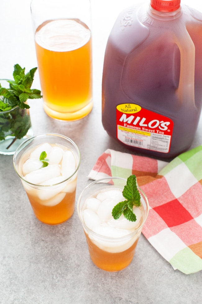 glasses with sweet tea vodka and lemonade with jug of Milo's Sweet Tea in the background, glass with fresh mint
