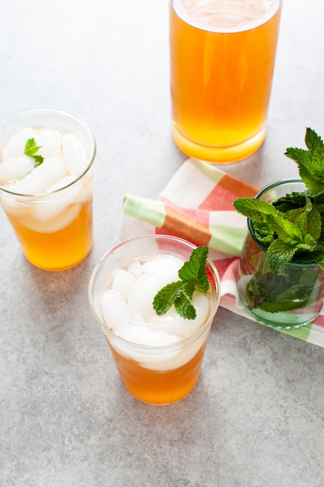 glasses with sweet tea vodka and lemonade with fresh mint in a glass in the background
