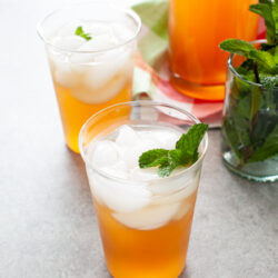 glasses with sweet tea vodka and lemonade with fresh mint in a glass on the side and a pitcher of the same drink in the background