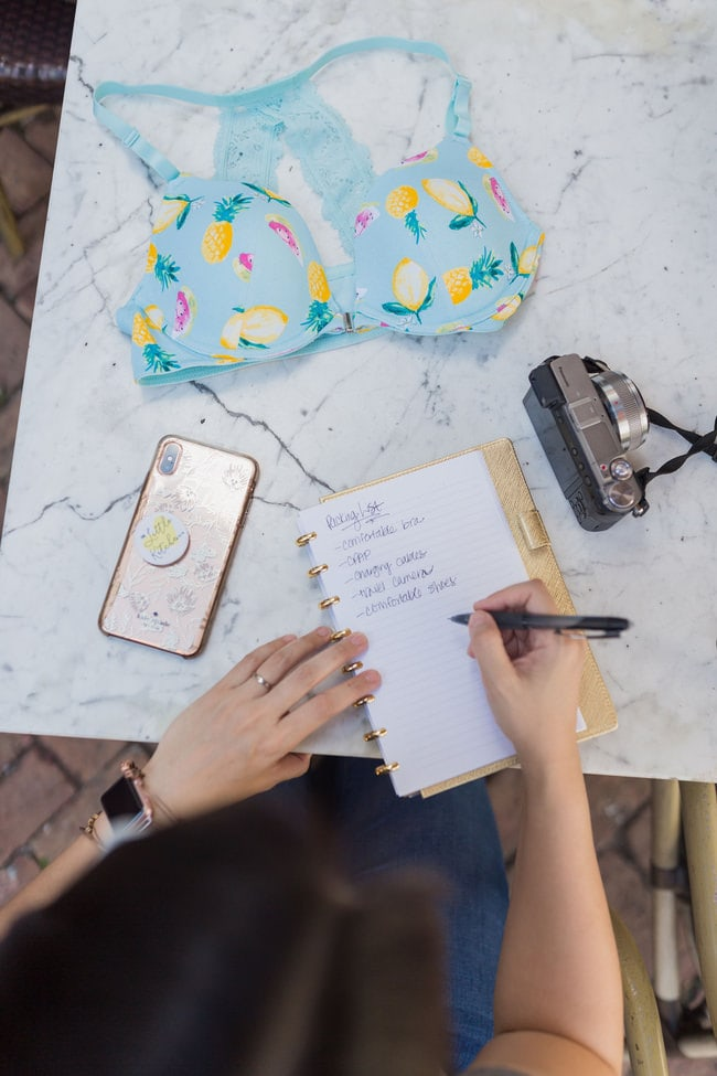a woman writing notes on a notebook with a camera, phone and bra on a table