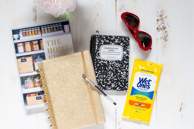 The Home Edit book, planner, pen, kindle, sunglasses and hand wipes