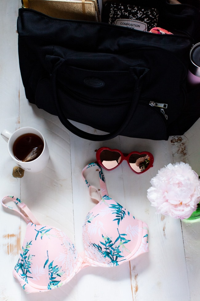 a pink bra on a table with a flower in a green vase, with sunglasses and a cup of tea and a black carry on bag