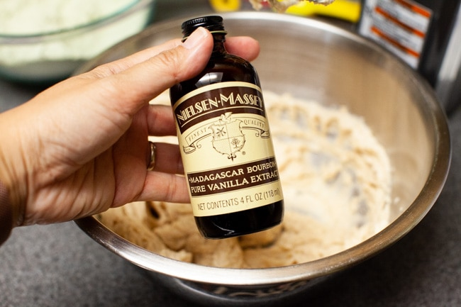 Hand holding bottle of vanilla extract with mixing bowl in background for Matcha Cookies from thelittlekitchen.net