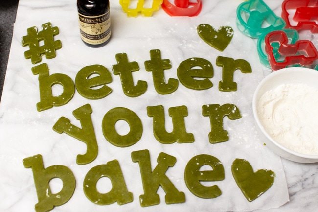 Matcha Cookie dough cut to spell #betteryourbake with bottle of vanilla, cookie cutters, and bowl of flour in background from thelittlekitchen.net