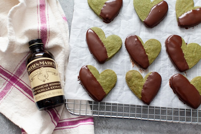 Heart Shaped Chocolate Dipped Matcha Cookies on cooling rack next to bottle of vanilla extract from thelittlekitchen.net