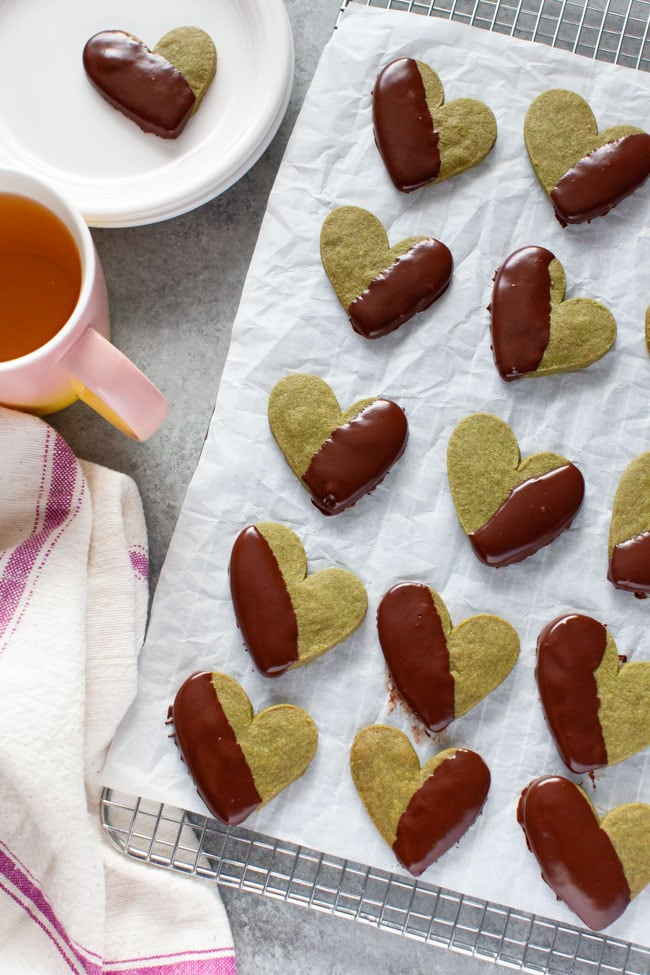 Chocolate Dipped Heart Shaped Matcha Cookies on parchment paper and cooling rack with kitchen towel, pink cup of tea, and cookie on plate in the background from thelittlekitchen.net