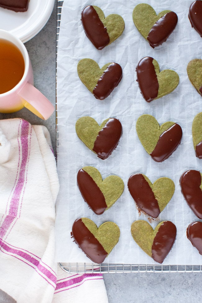 Heart Shaped Chocolate Dipped Matcha Cookies on white parchment paper, next to kitchen towel, cup of tea, and white plate from thelittlekitchen.net