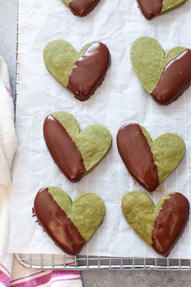 Heart Shaped Matcha Cookies Dipped in Chocolate on White Parchment Paper from thelittlekitchen.net