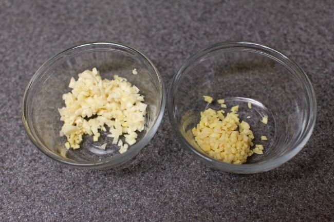Two glass bowls with minced ginger and garlic