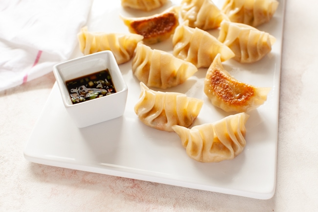 Vegan Dumplings on white serving tray with square dipping sauce bowl and kitchen towel in background from thelittlekitchen.net