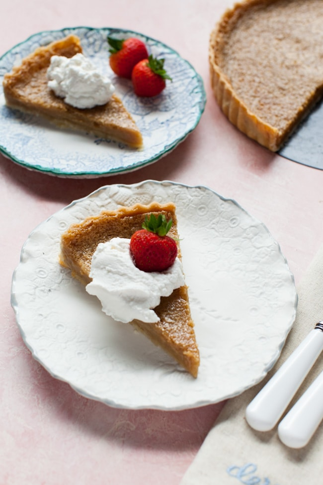 Slice of Sugar Pie on a white plate, topped with whipped cream and strawberry