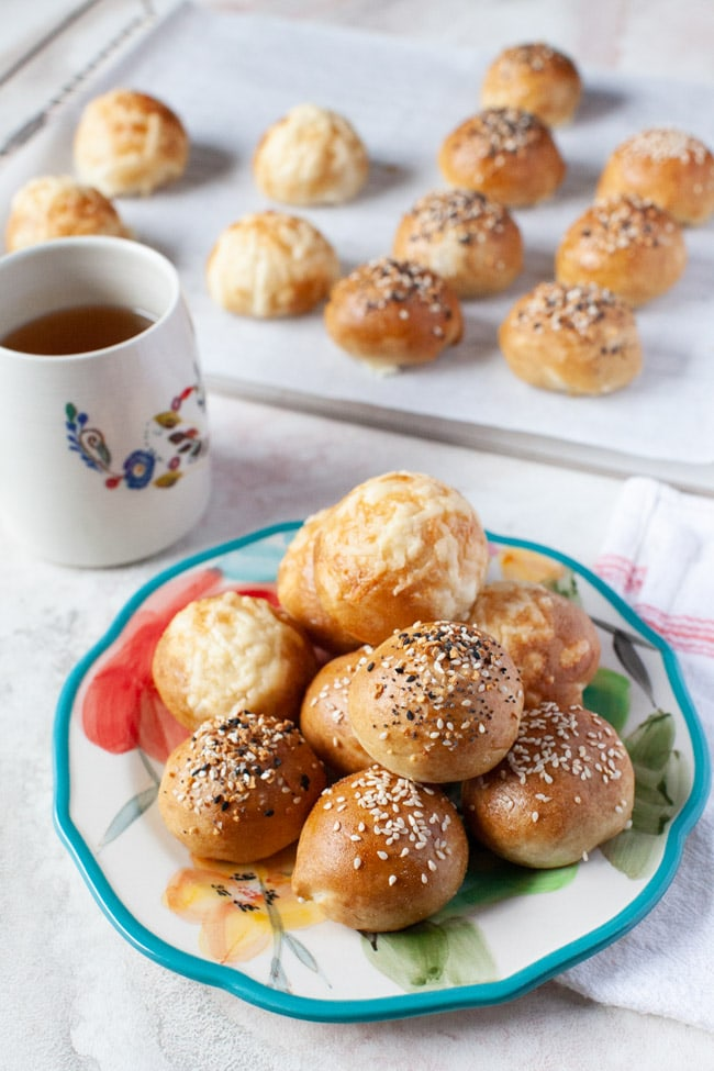 stuffed bagel bites on a floral plate with a cup of tea in the background along with more stuffed bagel bites