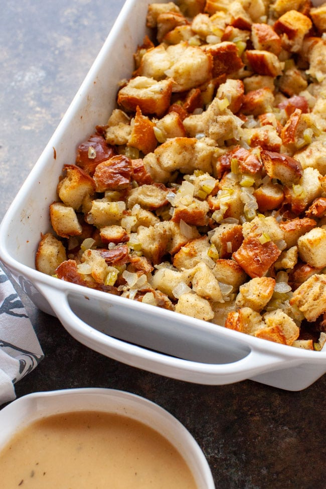 Cooked stuffing recipe in a white baking dish with a bowl of gravy in the foreground