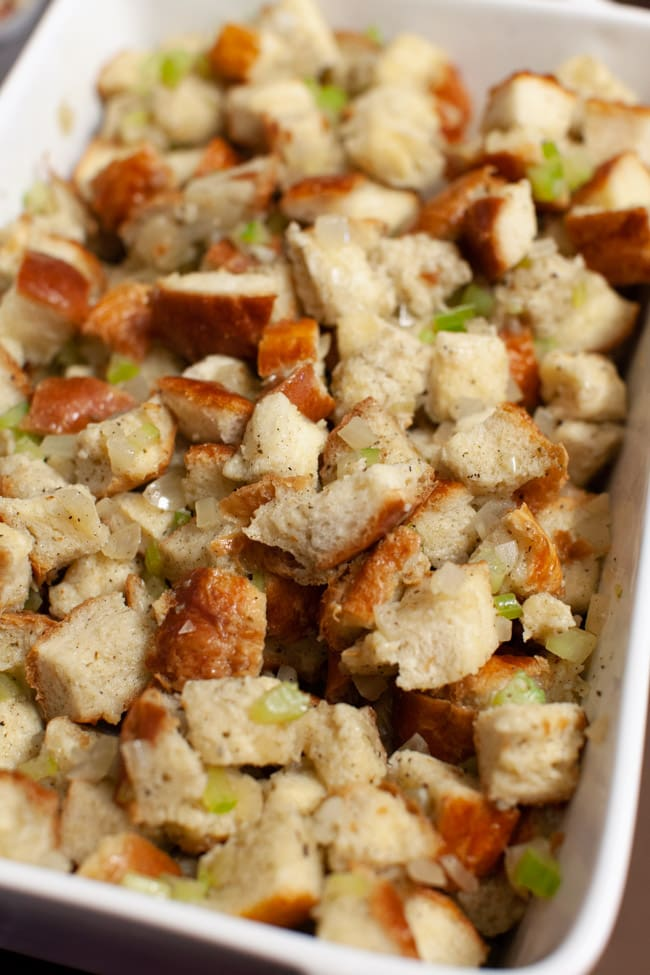 stuffing in a white baking dish before it goes into the oven