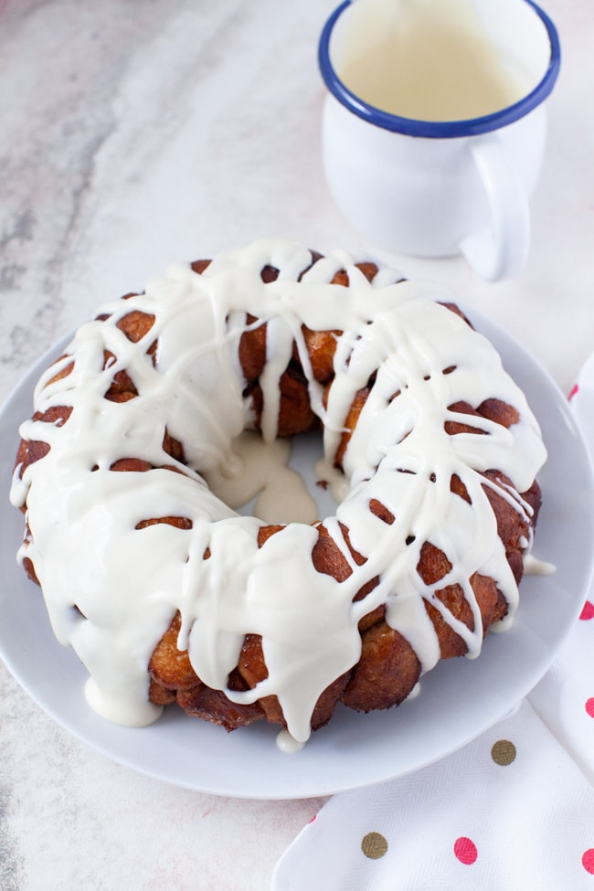 monkey bread on a plate with cream cheese frosting on top and a pitcher with frosting in the background