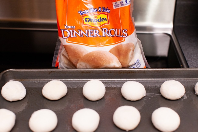 frozen yeast dinner rolls on a baking dish with a bag of Rhodes Dinner Rolls behind it