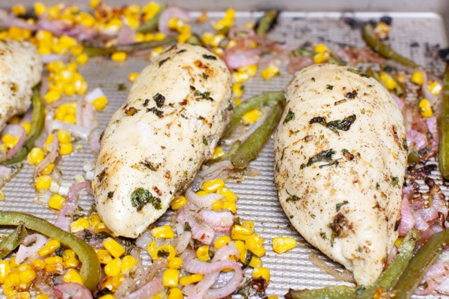chicken, red onions and bell peppers on a baking sheet