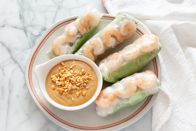 Vietnamese Spring Rolls with peanut dipping sauce on a plate with a napkin in the background