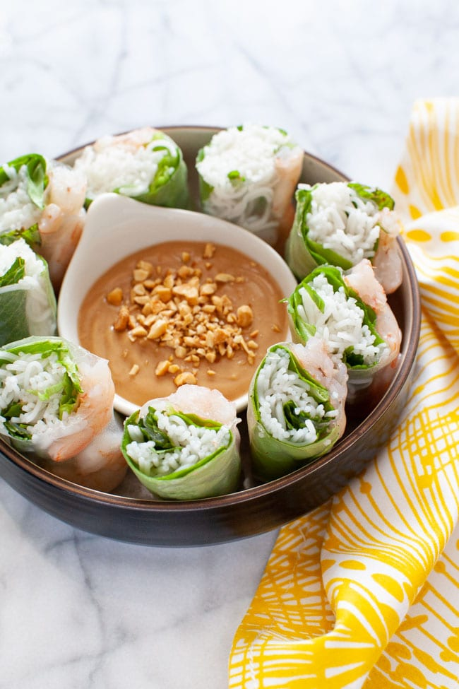 Vietnamese Spring Rolls cut up in a bowl with peanut dipping sauce on a plate with a napkin in the background